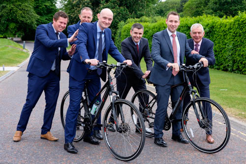NIGTA members Ronan McCanny, left and Vincent Shannon get on their bikes for the NIGTA cycle run with a bit of help from NIGTA members Robert Adams, Ben Frazer, Niall O'Donnell and Robin Irvine, NIGTA CEO. Photograph: Columba O'Hare/ Newry.ie